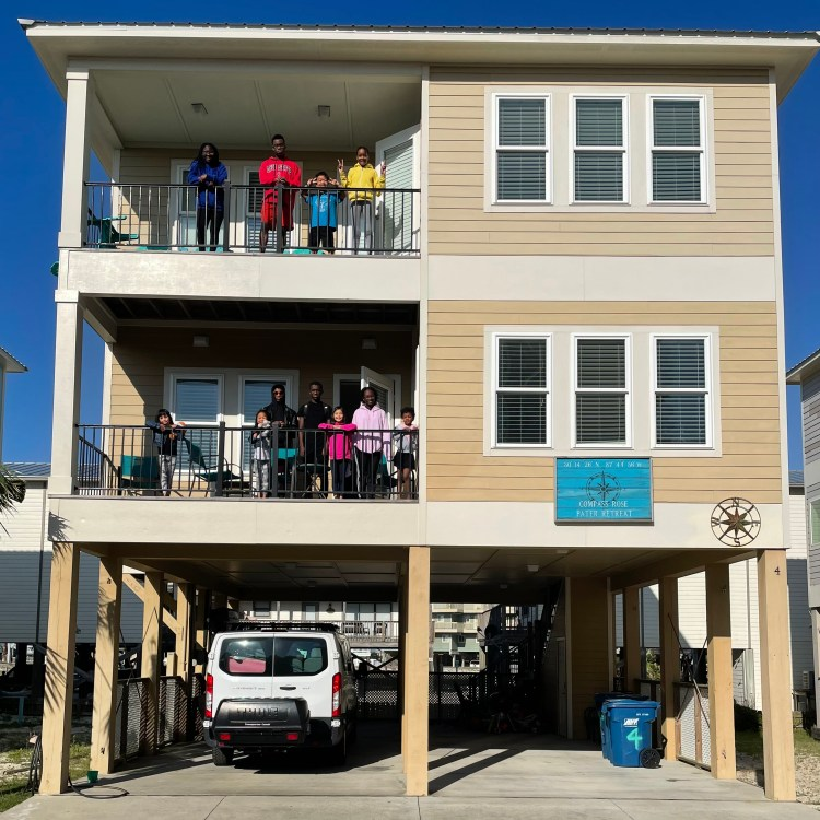 11 children standing on the outdoor decks of a beach house. They are positioned on two decks, one lower and one upper. They are looking at the camera, smiling or waving.