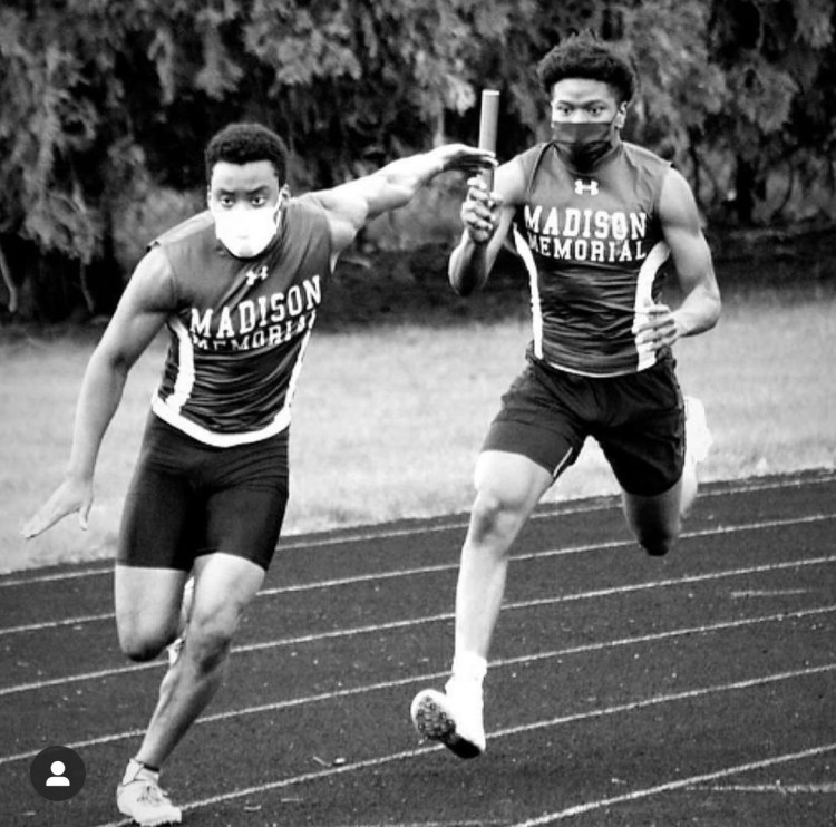 Cam, a Black man wearing a mask over his mouth and nose, is wearing a 'Madison Memorial, track singlet as he runs. He is looking very determined as a teammate hands the baton to him.