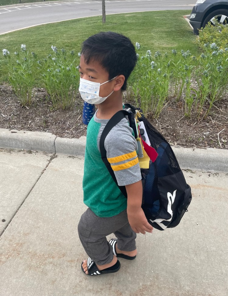Bowen, an Asian boy with Dwarfism, is walking on the sidewalk. He has a white mask with blue print on it. He has a t-shirt and grey joggers on. He is wearing Adidas slides. On his back is a black mesh backpack. His backpack has many ribbons and awards hanging from the loop at the top.