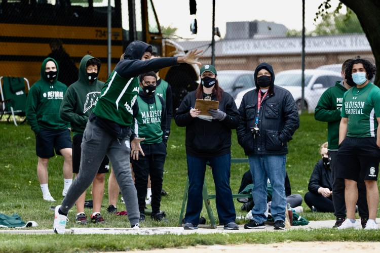 Jax, a Black boy, with a black hoodie under his track singlet is throwing a shot put. His teammates and coaches surround him watching.