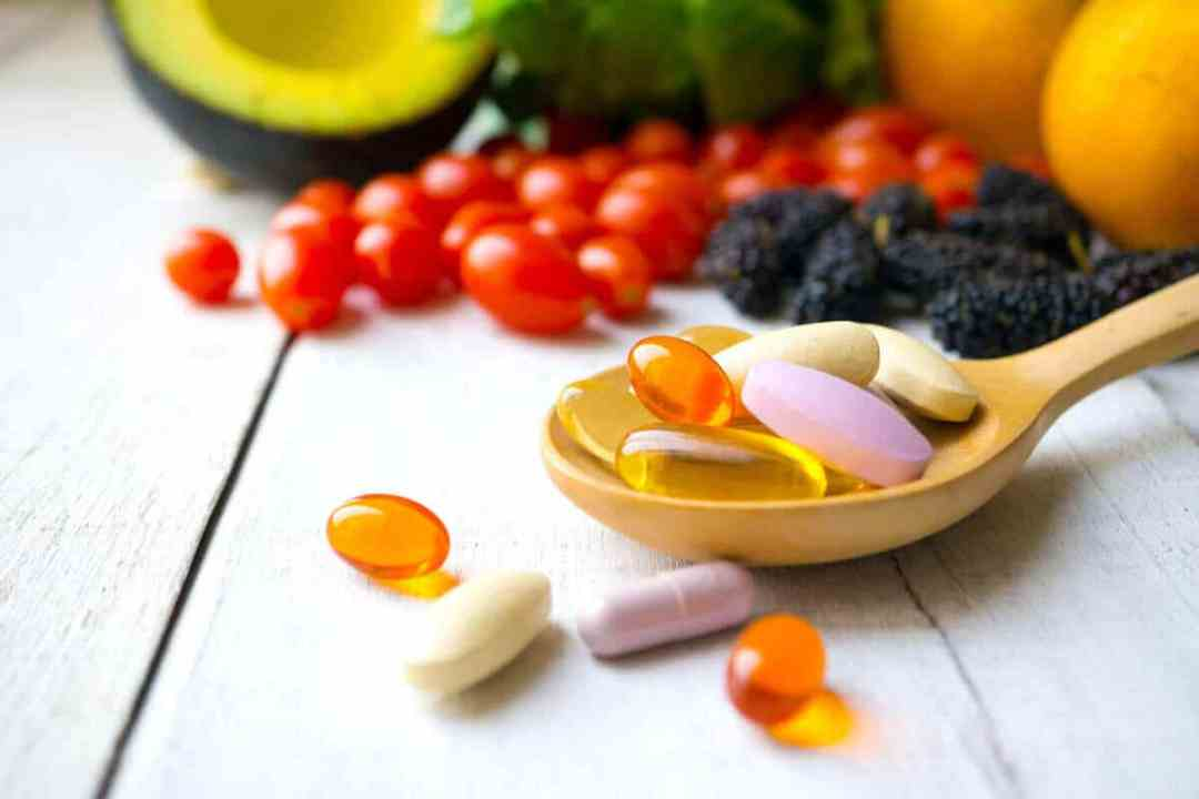 multivitamins on a wooden spoon with fruits in the background