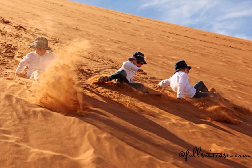 Children gliding down the sand dunes in Namibia