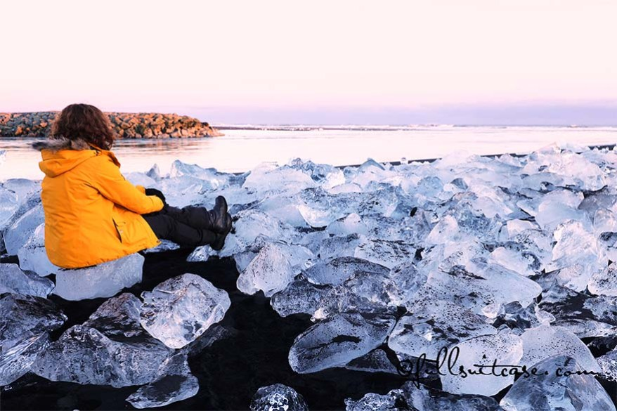 Hiker sitting in between many pieces of Ice on Jokulsarlon coast in Iceland