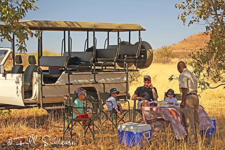 Family with kids having picnic lunch on safari in Africa