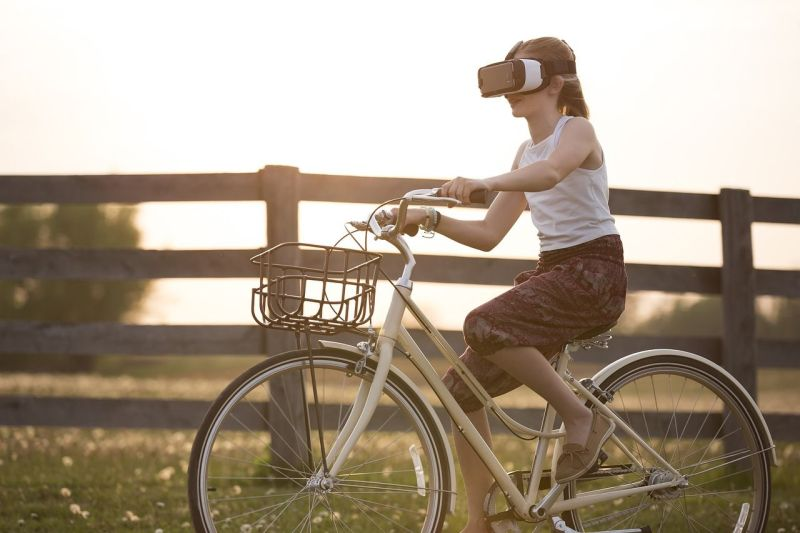 Girl riding a bike wearing a Virtual Reality headset