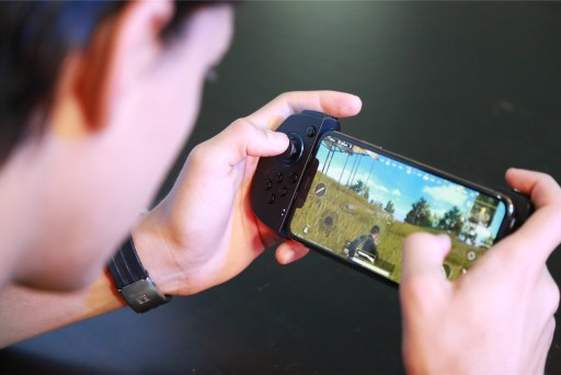 The GameSir G6S iPhone controller from front in man's hands showing PUBG on the phone screen
