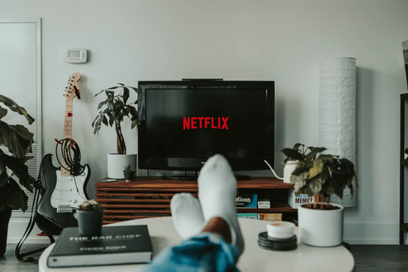 Netflix on a living room TV, with viewer sticking their feet up on a coffee table