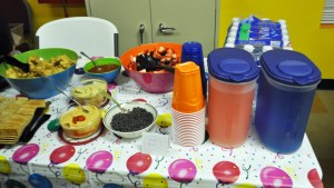 table of food for a birthday party including chips, salsa, hummus, chocolate chip Snipe bait, mixed berries, and koolaid
