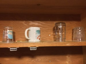 8 Things Parent Never Have Enough Of, a cupboard shelf with only four cups sparsely arranged on it