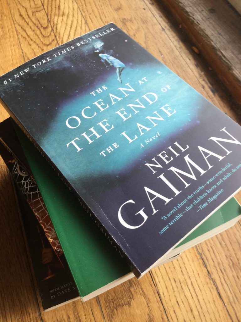 A stack of books by Neil Gaiman with his book The Ocean at the End of the Lane on top.