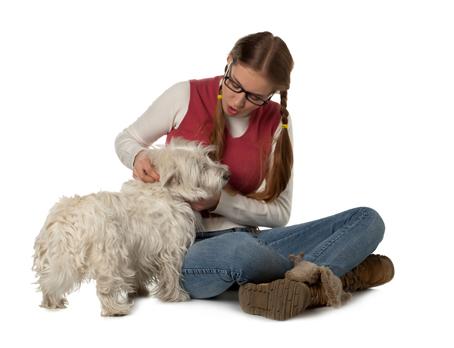 teenager playing her white maltese dog