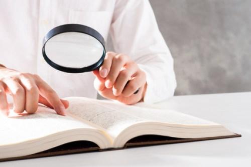 虫眼鏡を使って本を調べる男性