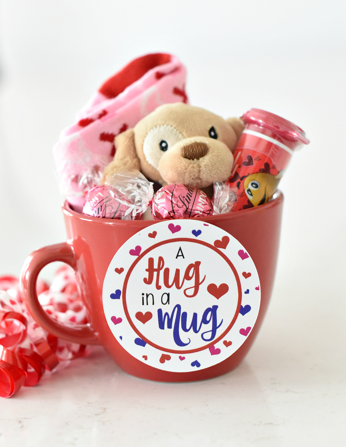 Valentines Gift Idea for kids-This cute Hug in a Mug gift is perfect to give your kids for Valentine's Day. Fill a cute mug with toys or candy and add this cute tag for a fun Valentine's gift idea for your kids. #valentines #valentinesday #valentinesdaygifts #valentinesdaygiftideas
