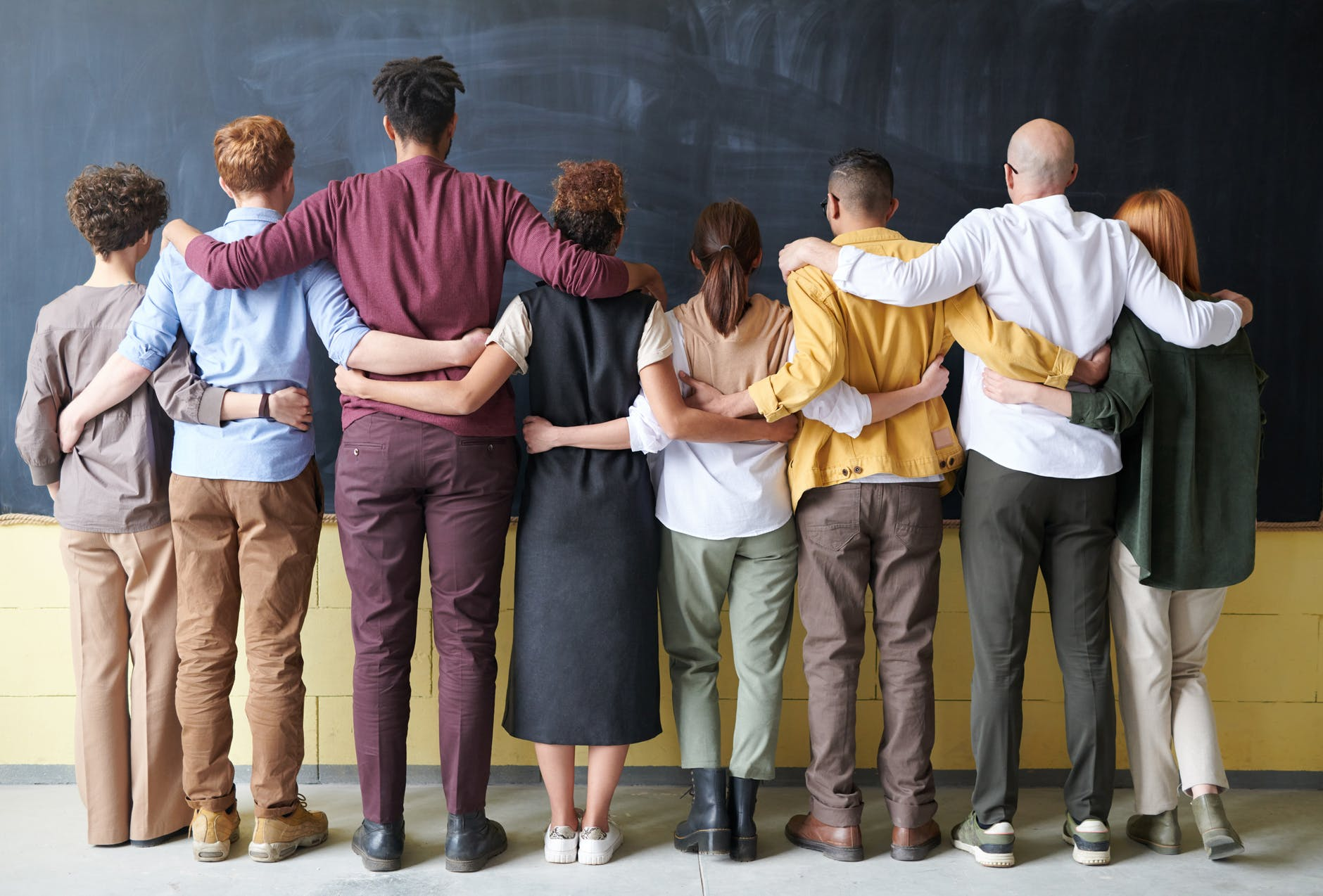 8 hombres y mujeres de diferentes edades, estaturas y complexiones físicas se abrazan representando la diversidad