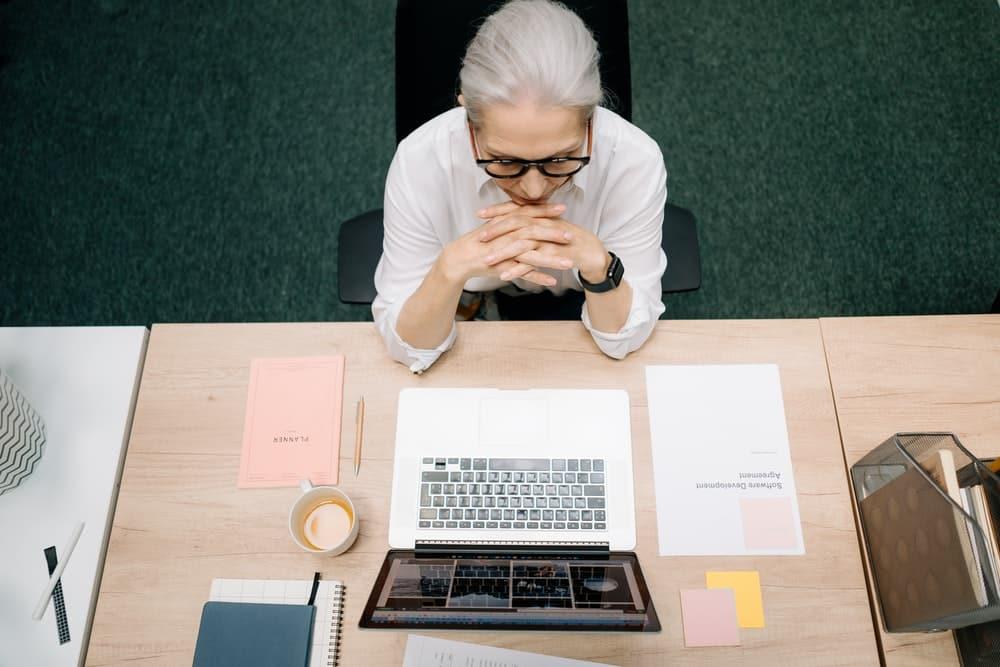 Mujer senior trabaja en un escritrio con un ordenador