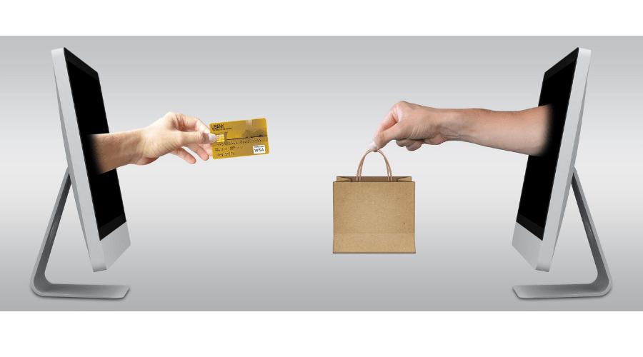 Dos computadores de frente y de una pantalla sale una mano con una tarjeta de crédito y de la otra pantalla sale una mano entregando una bolsa