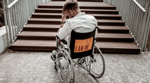 Hombre en silla de ruedas frente a una escalera