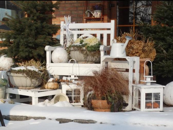 ogrody kapias - elementy ozdobne ogrodu zimą - ławka, konewki lampiony