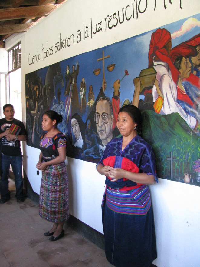 Two of the Franciscan sisters in Zacualpa tell the story behind the mural at the center which depicts the recent history of suffering and hope of the Quiche people.