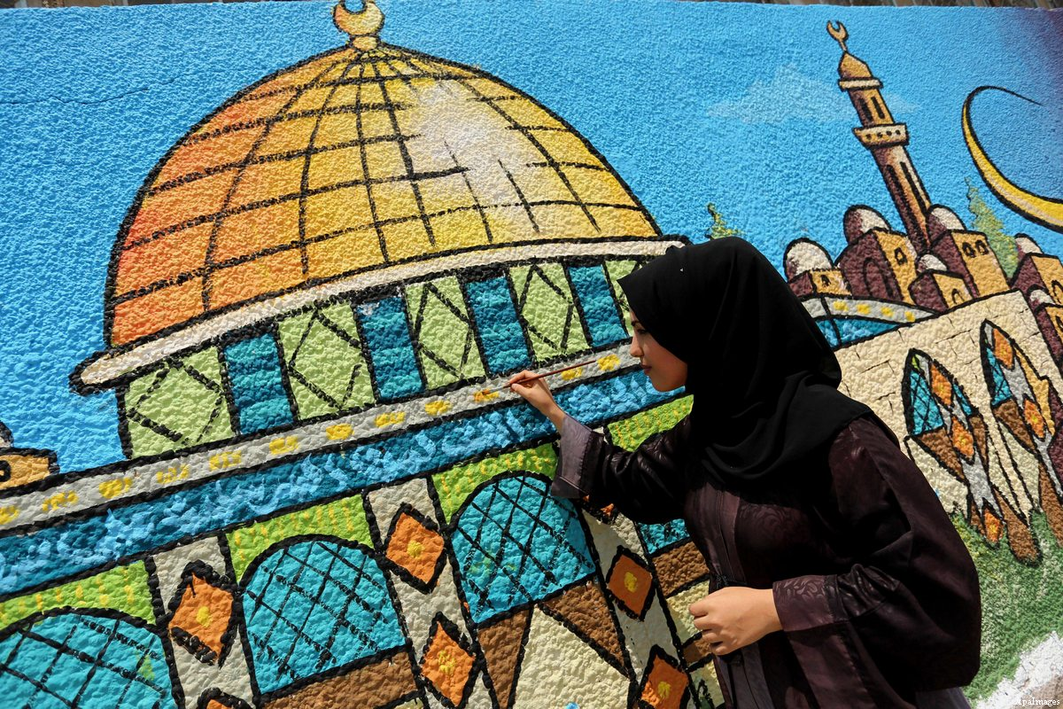 A Palestinian artist paints a mural depicting the Dome of the Rock in Gaza city on July 25, 2017 [Ashraf Amra / Apa Images]