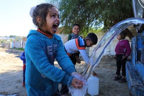 Palestinian girl washes hands with clean water