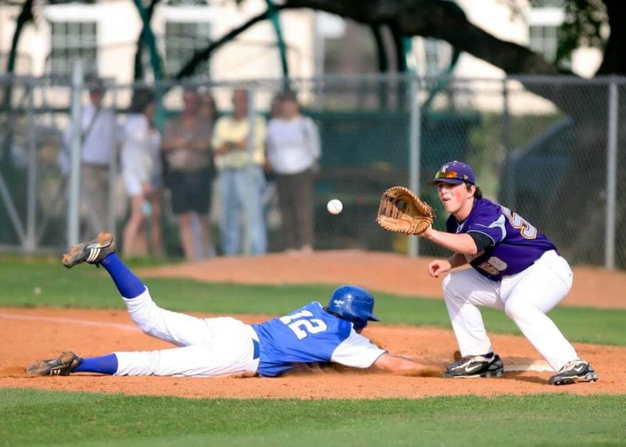 a baseball player slides into home plate as the catcher catches the baseball