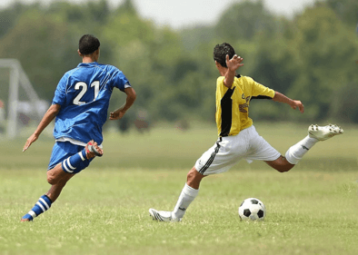 two men trying to kick soccer ball