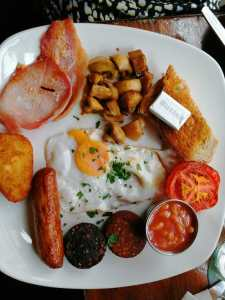 Fried egg, bacon, sausage, beans and toast on the plate