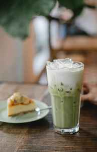 fresh matcha latte served on table with sweet pie