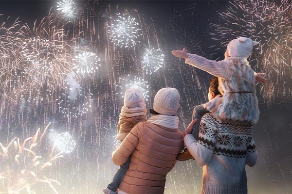 Parents and their two kids amazed by the New Year fireworks