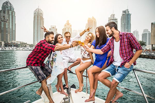 People cheering their beers while on a yacht