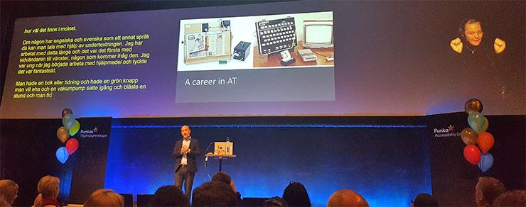 Talaren Hector Minto står mitt på scenen med texttolkning på en skärm ena sidan och en teckentolk på den andra.