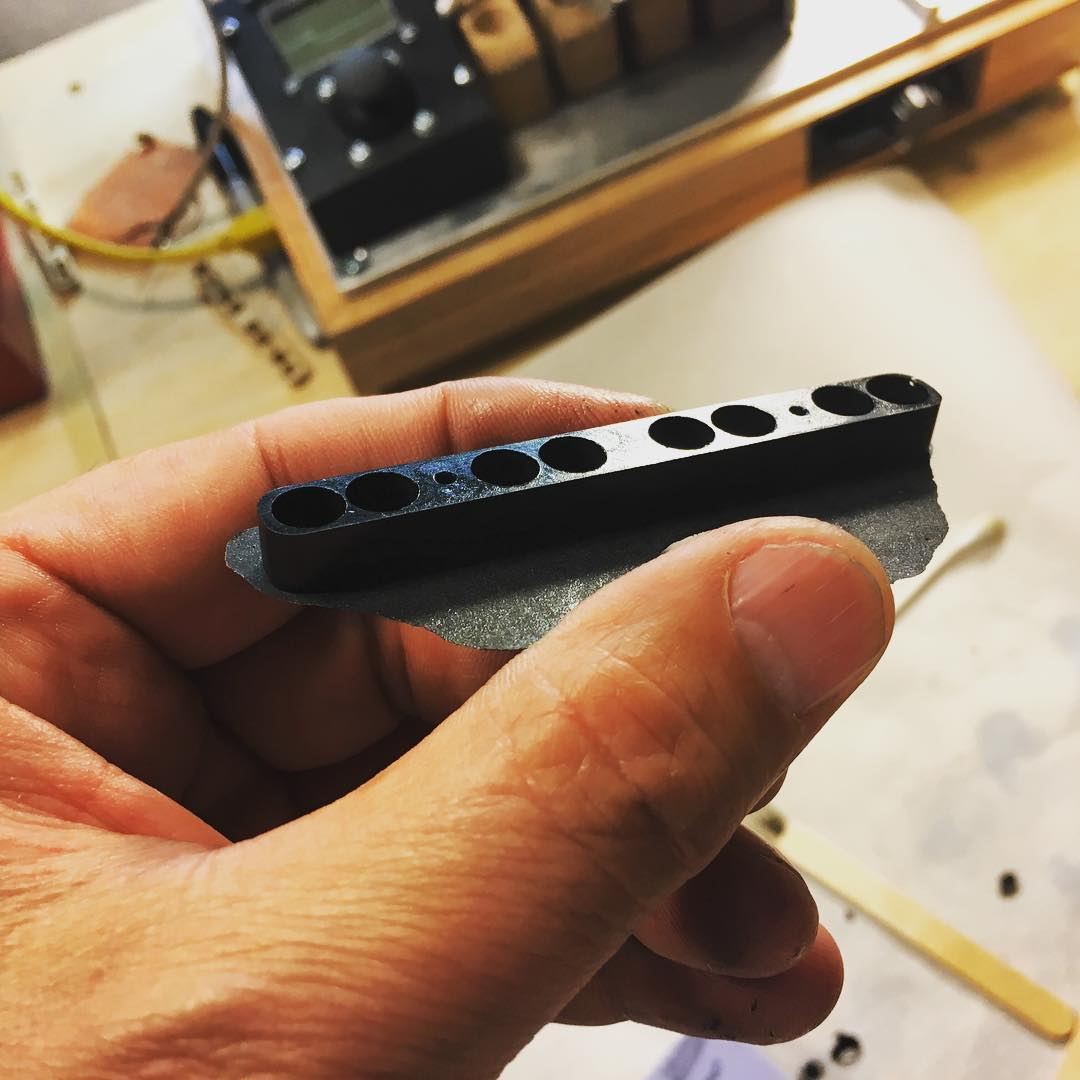 A polyurethane keeper I pulled from the mold. I still need to cut the flashing and sand the edge flat. Those little neodymium magnets are very strong and unruly. I designed this little cast keeper bar to keep them in place. #funktronicpickups #winding #handwoundpickups #basspickups #madscientist #neodymiummagnets #guitarpickups