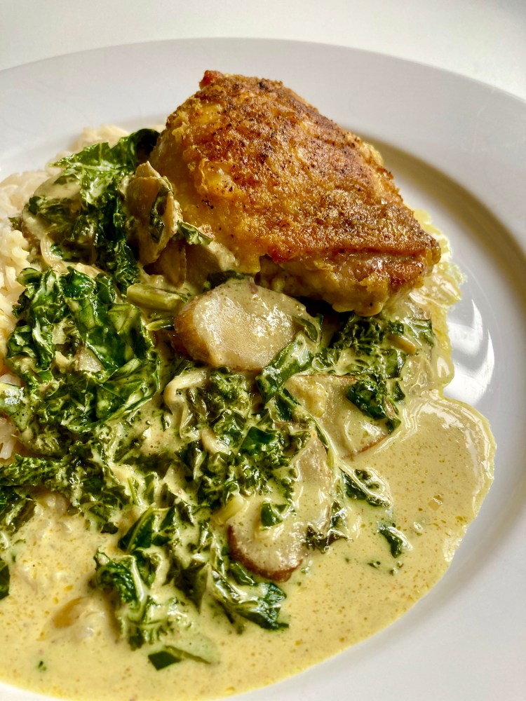 chicken with kale and burdock curried cream on a plate with rice
