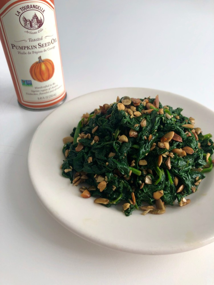 spinach salad with pumpkin seed oil bottle