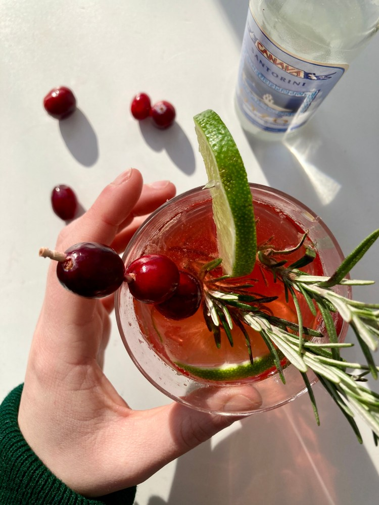 Ouzo Cranberry Spritz Cocktail holding a glass