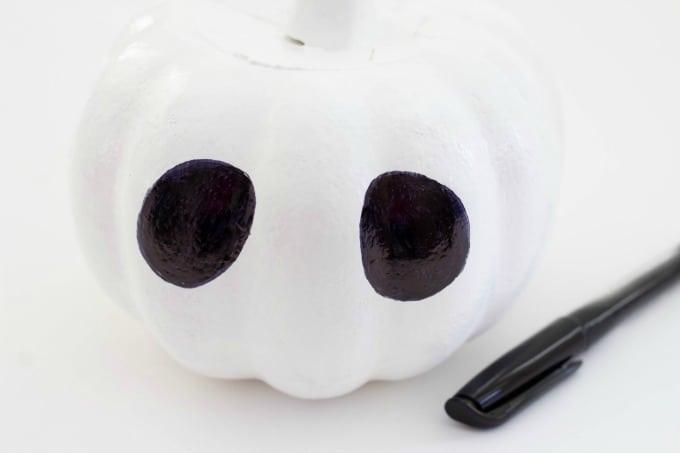 Make the eyes for your Jack Skellington pumpkin with black marker