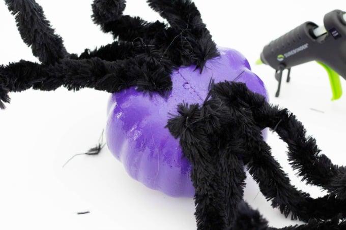 Glueing eight legs on spider pumpkin
