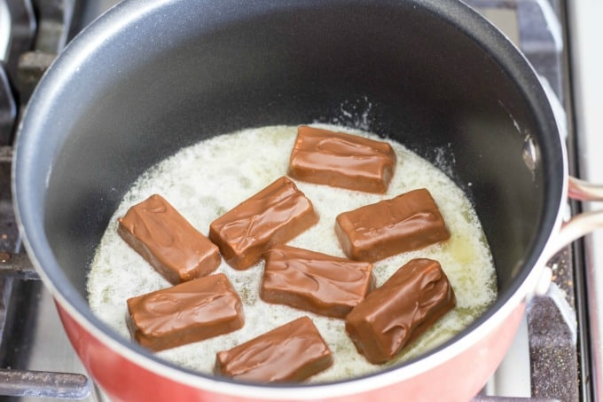 To make the party mix recipe, you'll have to first melt Snickers and butter together in a saucepan.