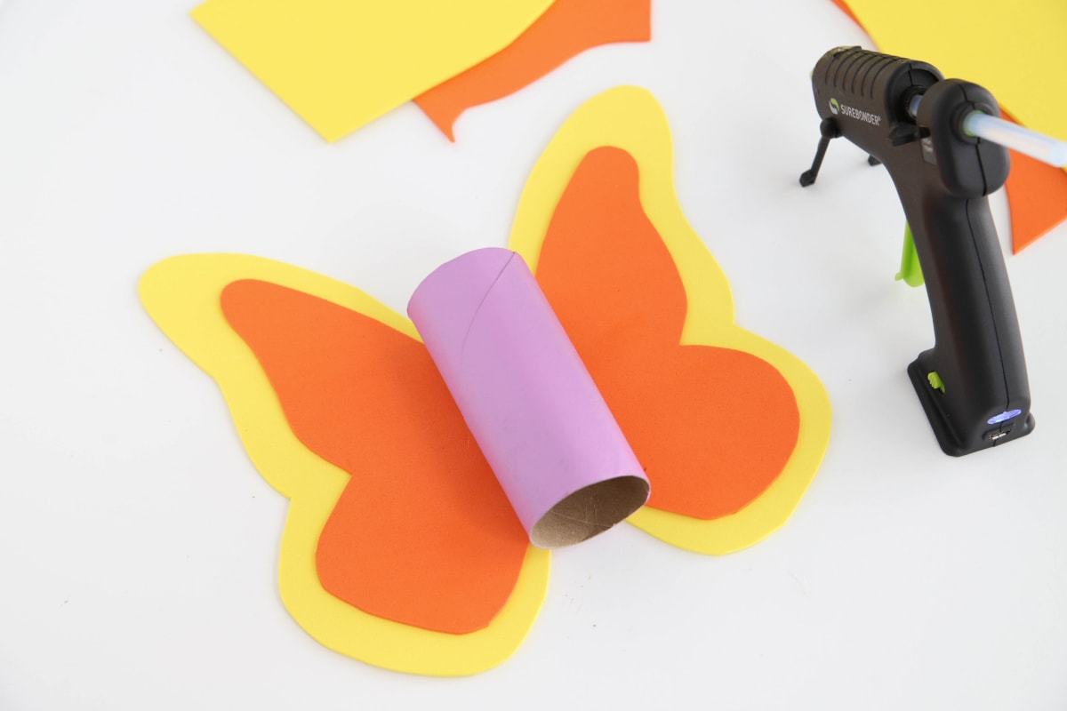 Gluing the pieces for a butterfly toilet paper roll craft