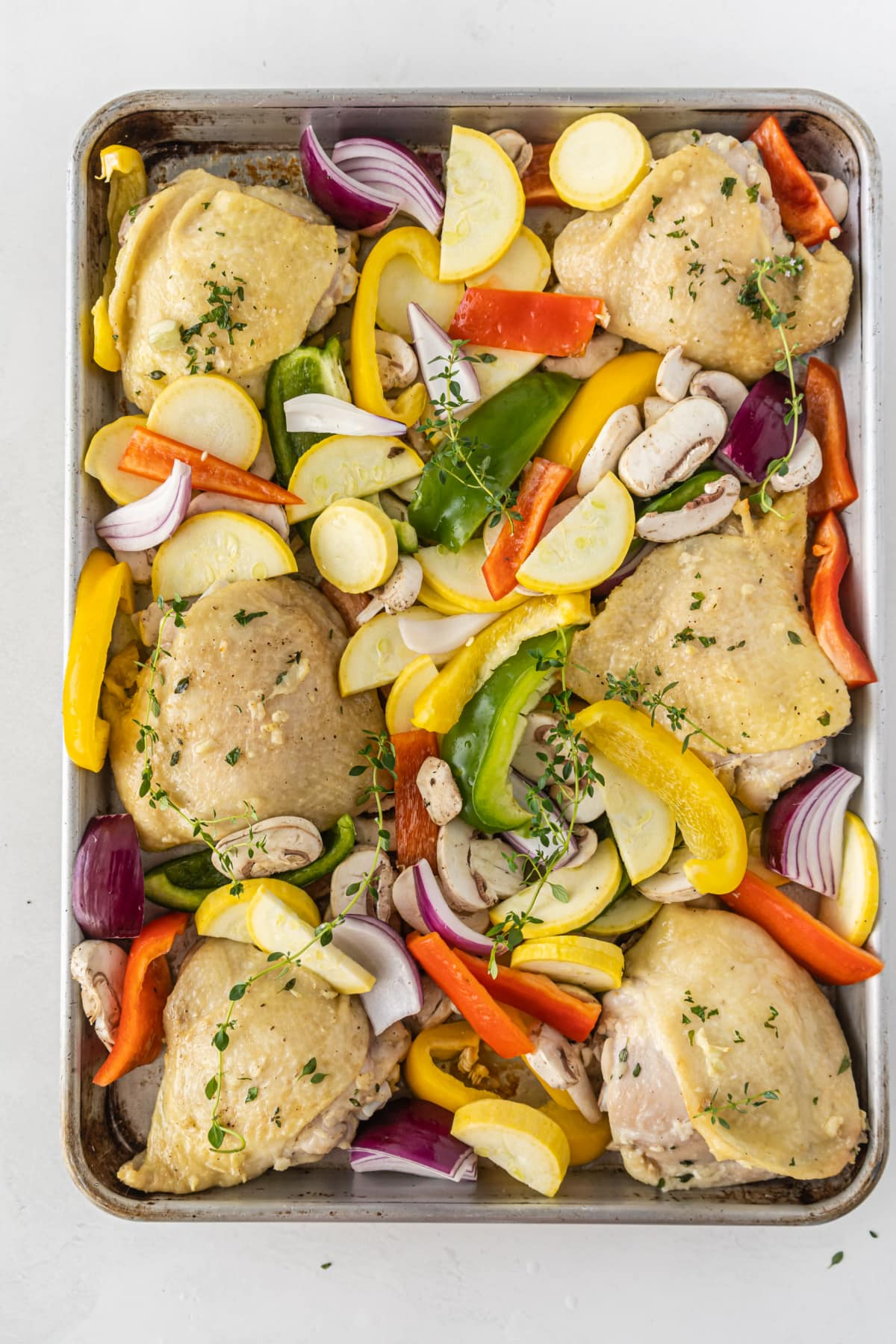 sheet pan chicken on baking sheet with veggies
