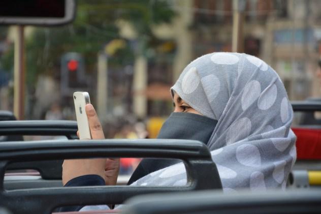 スマホをいじるムスリム女性