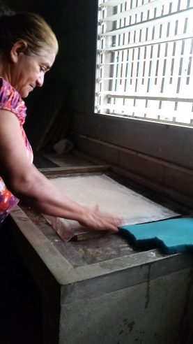 A woman patting the paper into shape