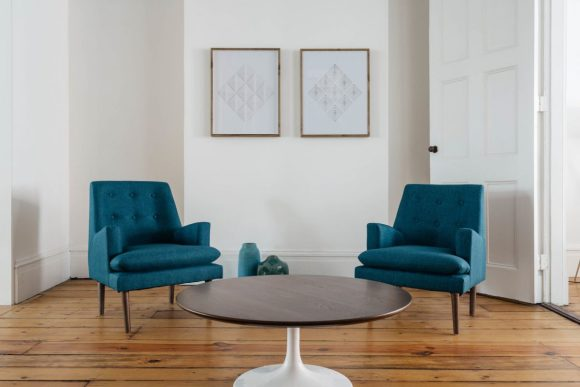 two teal chairs in a living room with white walls, a dark wood coffee table, and two minimal geometric art pieces on the wall