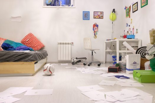 a messy white children's room with papers and toys everywhere