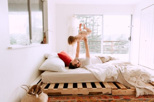 a father and child playing on a bed in a brightly lit bedroom with white walls and a wooden pallet bedframe