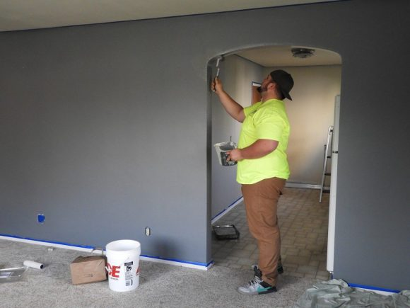 a man in a neon yellow shirt paints a wall in a house undergoing renovation