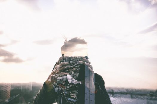 a double exposure photograph that shows the photographer and an image of the city overlaid