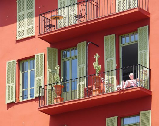 an older woman sits on her balcony beside potted cacti in a salmon colored building