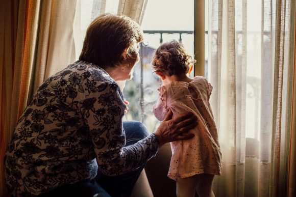 An older woman and a toddler stand together looking out a window. You can only see the backs of their heads.